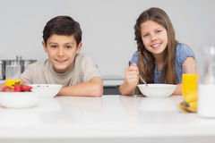 Smiling young siblings enjoying breakfast in kitchen Stock Photography