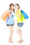 Smiling young sisters standing and holding shopping bags Stock Image