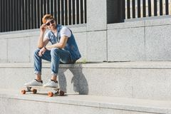 Smiling young skater sitting on stairs with longboard. Looking away Stock Photography