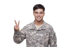 Smiling young soldier gesturing victory sign Royalty Free Stock Photo