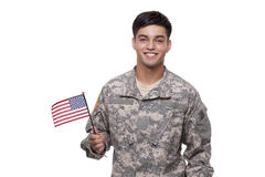 Smiling young soldier posing with an American flag Stock Photos