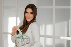 Smiling young sophisticated woman pulling the present ribbon. Delicate young woman in elegant white interior home, holding a beautiful present round box, pulling Stock Photos