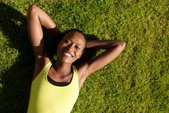 Smiling young sports woman relaxing on grass Stock Photos