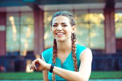 Smiling young sports woman smiling happy with smart watch royalty free stock photo
