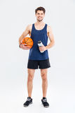 Smiling young sportsman holding basket ball and water bottle Stock Image