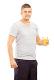 Smiling young sportsman posing with a glass of juice Royalty Free Stock Photos