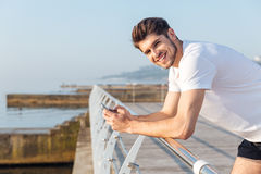 Smiling young sportsman using cell phone standing on wooden terace. Near the sea stock images