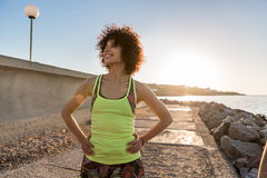 Smiling young sportswoman warming up before jogging outdoors Stock Image