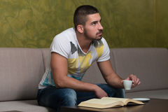Smiling Young Student In Cafe Reading Book. Young Male Student Drinking And Reading Book In Cafeteria Royalty Free Stock Image
