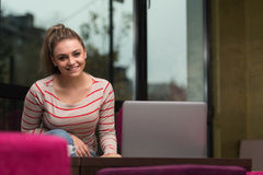 Smiling Young Student In Cafe Using Laptop Royalty Free Stock Photos