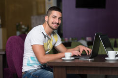 Smiling Young Student In Cafe Using Laptop Royalty Free Stock Image