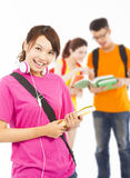 Smiling young student holding books and earphone with classmates Royalty Free Stock Photography