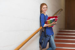 Smiling young student holding her notes on the stairs Stock Images
