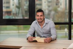 Smiling Young Student In Library Reading Book Stock Images