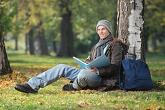 A smiling young student seated on a green grass and reading a bo Royalty Free Stock Photography