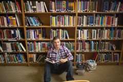 Smiling young student sitting on library floor reading Stock Photo