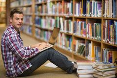 Smiling young student sitting on library floor using laptop. In college Stock Image