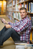 Smiling young student sitting on library floor using tablet. In college Stock Photos