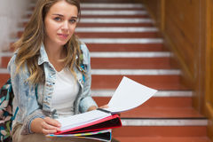 Smiling young student sitting on stairs looking at camera Stock Photography