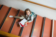 Smiling young student sitting on stairs looking up at camera Royalty Free Stock Photo