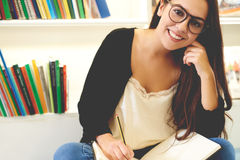 Smiling young student sitting studying Stock Images