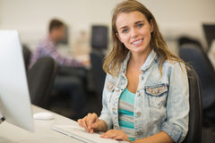 Smiling young student studying in the computer room Stock Image