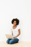 Smiling young student using a laptop computer Stock Photography