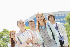 Smiling young students standing together at college campus Stock Image