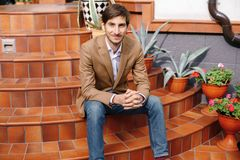 Smiling Young Stylish Man Sitting Outdoors On Vintage Circular S Stock Images