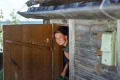 Smiling young suntanned woman with a rural door Stock Images