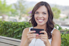 Smiling Young Teen Female Texting on Cell Phone Outdoors. Attractive Smiling Young Adult Female Texting on Cell Phone Outdoors on a Bench Stock Image