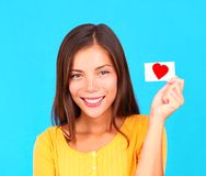 Smiling young teen girl holding card sign in hand. Young woman showing her valentine card with a heart on it, on a bright blue background Stock Image