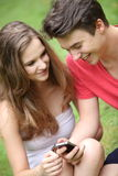 Smiling young teenagers using a mobile Stock Photos
