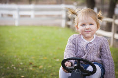 Smiling Young Toddler Smiling and Playing on Toy Tractor Outside Stock Image