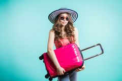 Pretty young woman in striped hat holding a pink suitcase on blue background and looks at the camera with a smile royalty free stock photography