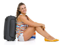 Smiling young tourist woman sitting near wheel bag. On white Stock Photo