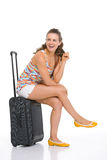 Smiling young tourist woman sitting on wheel bag Royalty Free Stock Photography