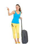 Smiling young tourist woman with wheel bag Stock Photos