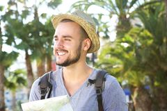 Smiling young traveling guy holding map outside Royalty Free Stock Photos