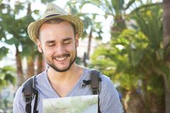 Smiling young traveling man looking at map Stock Photo