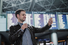 Smiling young traveller man at the airport makes selfie in front of timetable board.  Stock Photo