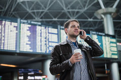 Smiling young traveller man at the airport talking on phone in front of timetable board. Smiling young traveller man at the airport talking on the phone in front Stock Photography