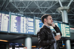 Smiling young traveller man at the airport talking on phone in front of timetable board. Smiling young traveller man at the airport talking on the phone in front Royalty Free Stock Photo
