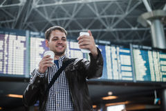 Smiling young traveller man with a coffee at the airport makes selfie in front of timetable board.  Stock Photo