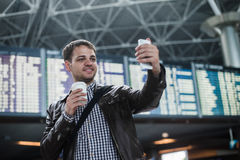 Smiling young traveller man with a coffee at the airport makes selfie in front of timetable board.  Royalty Free Stock Photography