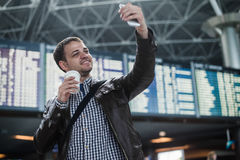 Smiling young traveller man with a coffee at the airport makes selfie in front of timetable board.  Stock Images
