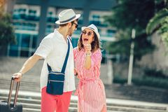 Young travellers couple looking for hotel. Smiling young travellers couple looking for hotel royalty free stock image