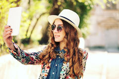 Smiling young trendy hipster girl on city background in the sunlight outdoor Stock Images