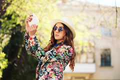 Smiling young trendy hipster girl on city background in the sunlight outdoor Royalty Free Stock Image