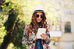 Smiling young trendy hipster girl on city background in the sunlight outdoor Royalty Free Stock Photo